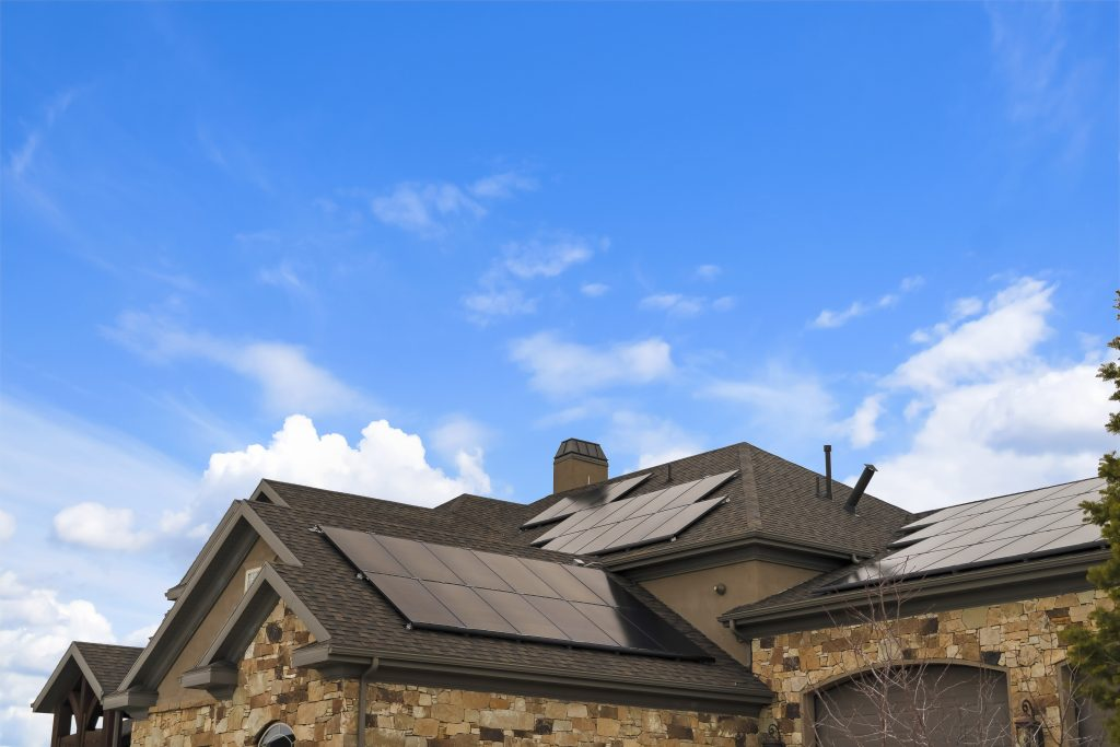 Cloudy blue sky over a home with solar panels on the pitched roof. The house also features stone exterior wall and arched garage door.
